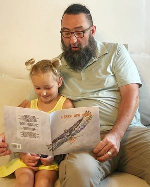 """A father and daughter read """"A Brush with Nature,"""" Red-tail Land Conservancy's first book, a collection of poetry and paintings featuring local areas preserved by Red-tail."""