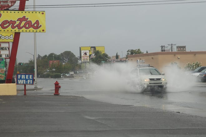 A vehicle powers through a puddle on Solano Drive on Monday, June 28.