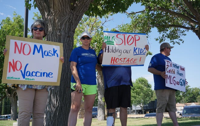 Parents hold signs at an anti-mask rally outside the Lake Carlsbad Beach Park on June 6, 2021.