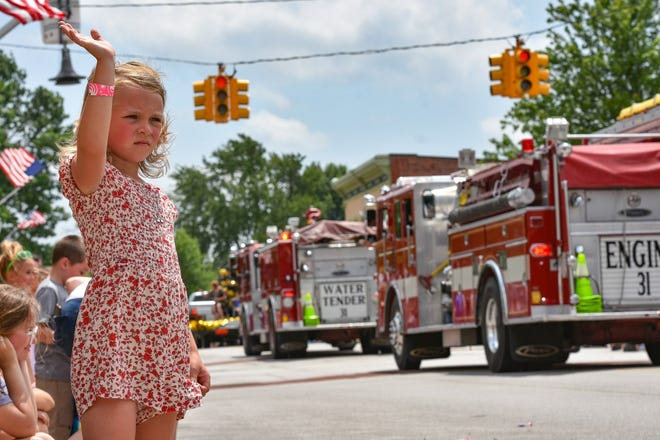 A hot but happy Annabelle George of Curtis waves to parade floats during the annual Genoa Homecoming parade on Saturday afternoon.