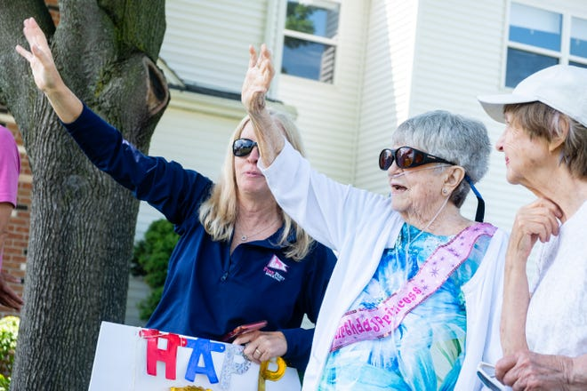 Marcia Haynes, second from right, waves as cars drive past Monday, June 28, 2021, in Port Huron. A drive-by parade was organized to help Haynes celebrate her 90th birthday.