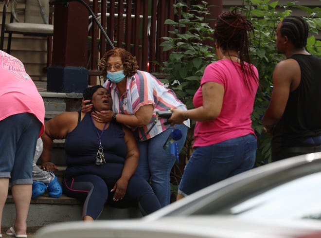 Three people were found dead at 552 Grand Ave. in Rochester on June 26.  A woman wearing a Rochester police civilian badge, comforts a relative who found out about the deaths.