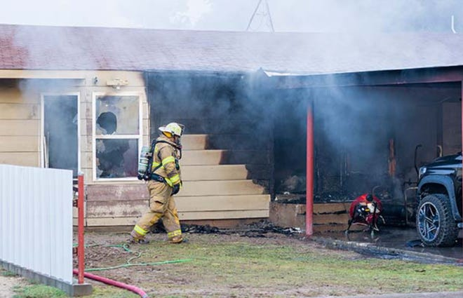A firefighter walks in front of a home in Big Lake on Monday, June 28, 2021. A fire claimed the life of a young girl inside the home.