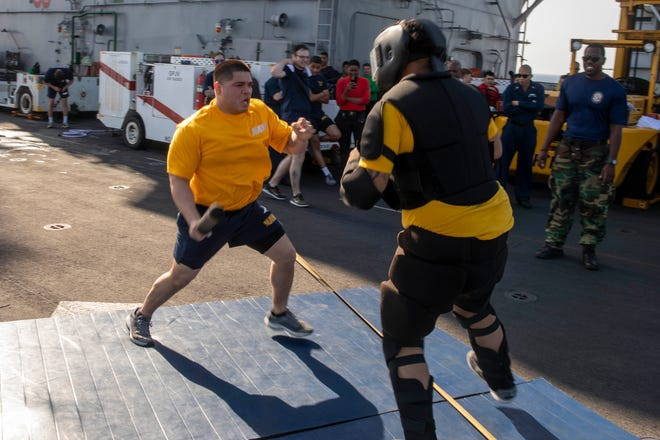 RED SEA - Aviation Ordnanceman 1st Class Augustin Regino, assigned to the Wasp-class amphibious assault ship USS Iwo Jima (LHD 7), performs a baton strike after getting sprayed with Oleoresin Capsicum (OC) during a Security Reaction Force Bravo (SRF-B) training, June 24, 2021. Iwo Jima is deployed to the U.S. 5th Fleet area of operations in support of naval operations to ensure maritime stability and security in the Central Region, connecting the Mediterranean and Pacific through the western Indian Ocean and three strategic choke points. (U.S. Navy photo by Mass Communication Specialist Seaman Isaac A. Rodriguez)