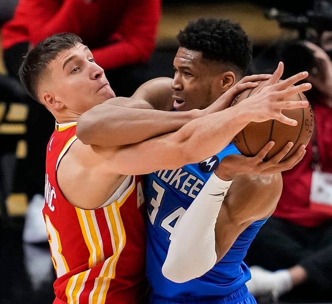 East finals: The Milwaukee Bucks' Giannis Antetokounmpo tries to protect the ball defended by the Atlanta Hawks' Bogdan Bogdanovic in the first half of Game 3 at State Farm Arena.