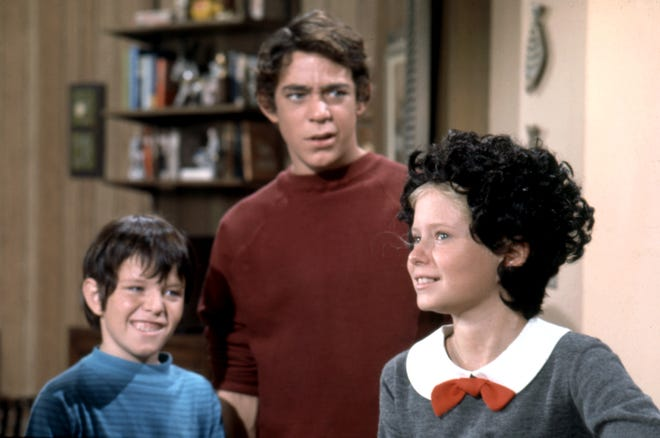 """Bobby (Mike Lookinland, left) and Greg (Barry Williams) poke fun at Jan (Eve Plumb) 's new look in """"Will the real Jan Brady get up?"""""""
