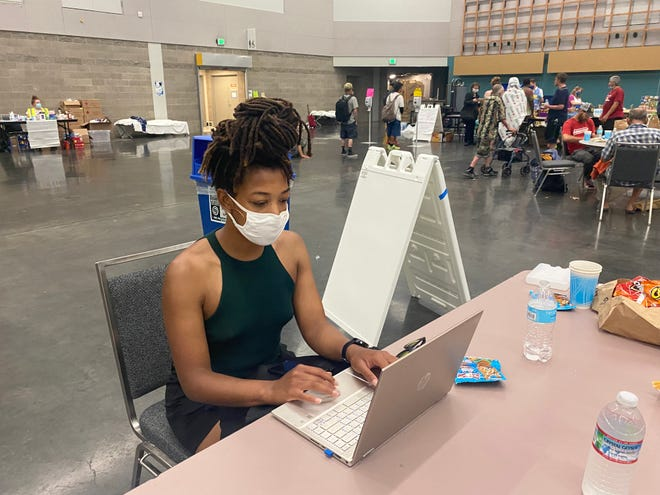 M.J. Jackson works at her laptop at the Oregon Convention Center, which doubled as a 24-hour cooling station over the weekend as Portland experienced a record-setting heat wave that exceeded 112 degrees.