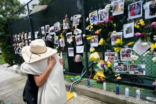 People embrace at a make-shift memorial outside St. Joseph Catholic Church, in Surfside, Fla., Monday, June 28, 2021, near the collapsed building for people still missing or dead. Many people were still unaccounted for after Thursday's fatal collapse.