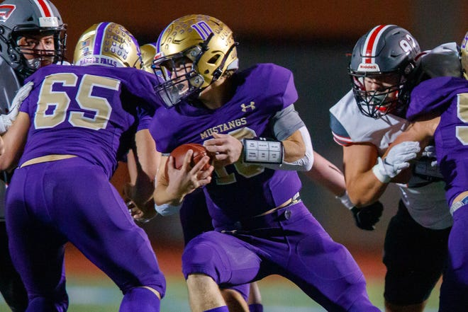 Marble Falls quarterback Jake Becker spins for yardage behind his offensive line in a playoff game against Sharyland Pioneer last season. Behind senior returning starters Hudson McBryde and Gerardo Hernandez, the Mustangs' offensive front looks like a team strength.