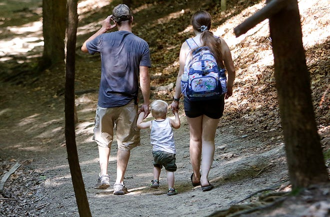 Michael and Meghan Blystone hold the hands of their son Bennett as they hike on the Lyons falls trail at the Mohican State Park on Tuesday, June 29, 2021. TOM E. PUSKAR/TIMES-GAZETTE.COM