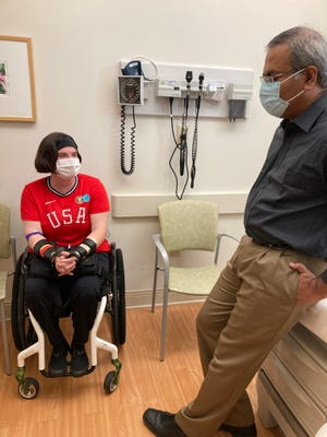 Dr. Cassie S. Mitchell, left, who is getting ready to compete in her third Paralympics in Tokyo in August, discusses how to handle her ongoing chemotherapy with Dr. Vamsi Kota at Georgia Cancer Center at Augusta University.