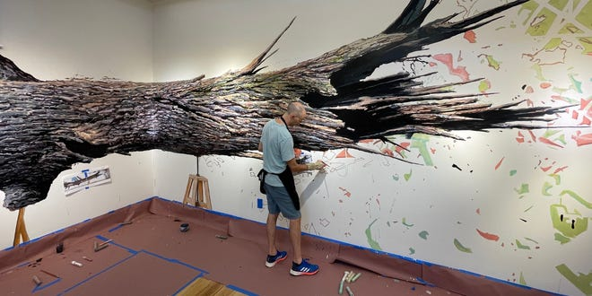 """Ethan Murrow works to create a 75-foot drawing of a fallen tree that spans three walls at the Cahoon Museum, for the exhibit """"The Greenhouse."""""""