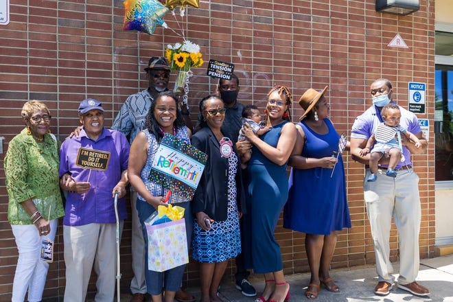 Sylvia Miles-Wright, third from left, smiles for a picture at W.R. James Elementary on her last school day as principal.