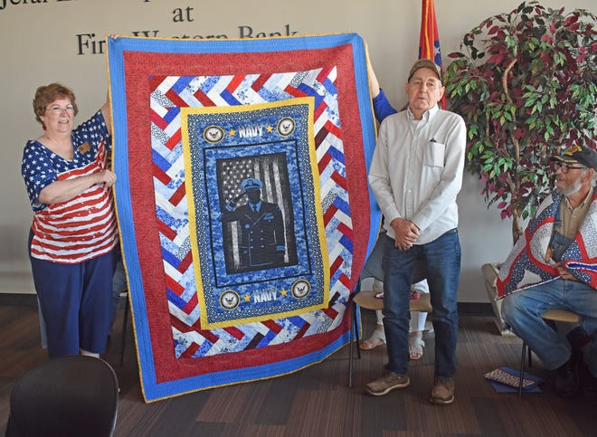 U.S. Navy veteran Bobby Hester stands beside his Quilt of Valor during the quilt presentation ceremony.