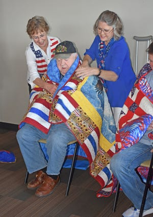 U.S. Army veteran David Beeler is seen being wrapped in his Quilt of Valor by members of the River Valley Stars.