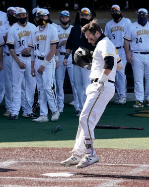 Adrian College's Gunner Rainey jumps on home plate after hitting a home run during a game in the 2021 season.