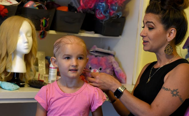 Shawna Vore, of Dundee starts to braid the hair of her daughter Aleena Smith, 6, after using Clobetasol topical foam medicine on her head before putting on the blond wig as she gets ready for school on her birthday.