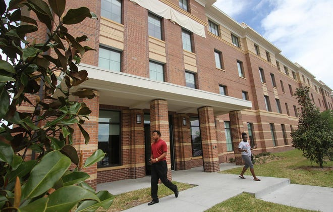 Students pass the Thomas and Joyce Hanks Moorehead Residential Life Center on the campus of Bethune-Cookman University. The dorms were built in 2016, but a dispute with a developer over the cost and financing terms led to a lengthy court battle.