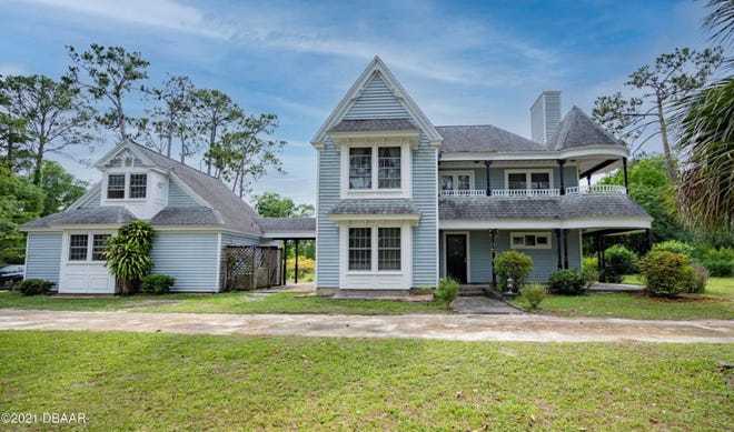 This Victorian-style home in Ormond Beach is beautifully situated on five acres that shares semi-private pond to the rear of the property.