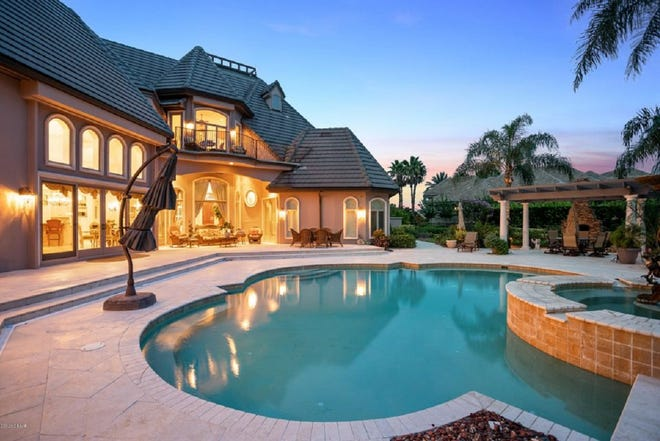 The resort-style outdoor-living space of this Plantation Bay home features a tumbled-marble pool area, pool house, a custom fountain and a pergola, with a wood-burning fireplace.