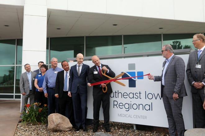 Great River Health President and CEO Matt Wenzel and others take part in a ribbon cutting ceremony Tuesday marking Great River Medical Center in West Burlington and Fort Madison Community Hospital becoming one hospital with two locations outside the Great River Medical Center main entrance in West Burlington. The new name will be Southeast Iowa Regional Medical Center.