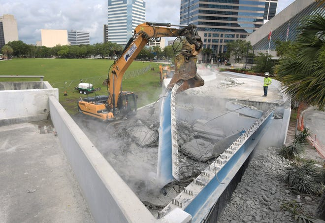 A worker monitors progress as heavy equipment from United Demolition pulls away metal beams that supported a portion of the southbound ramp to the Main Street bridge.