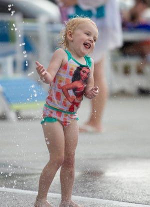 A young girl plays in the splash pad during Monday's opening event for the Kirksville Aquatic Center.