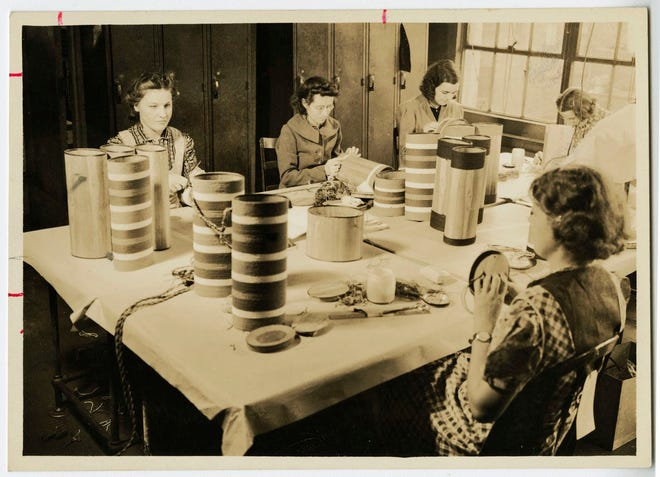 Blind Artisans of New England are shown at work in the shop in South Boston in 1940. The women work on tall striped canisters made of wood. Learn more from Digital Commonwealth at www.digitalcommonwealth.org.