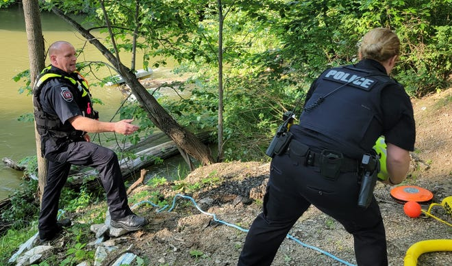 Huron Township Police officers prepare to rescue a kayaker in the Huron River Sunday night.