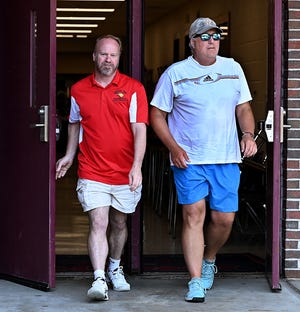 Westborough boys tennis coach Len O'Neil (right) and Brookline boys tennis coach Mike Mowatt (left) emerge during a lengthy meeting inside air-conditioned Westborough High School during discussions on where and when to play the Division 1 state championship after Tuesday morning's match was postponed due to the heat, June 29, 2021. After initially discussing an option to play an indoor match on Tuesday, tournament officials and coaches agreed to try again on Wednesday at 5:00 p.m. at Westborough High School.