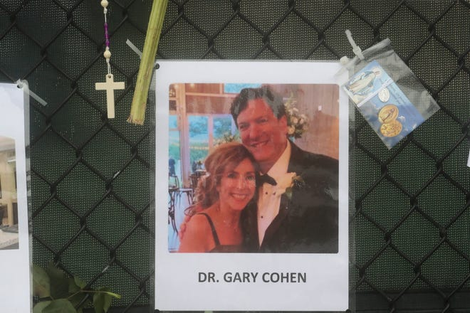 Shown is Dr. Gary Cohen (the woman was unidentified). Posters of some of the people missing from the Champlain Towers south condo collapse in Surfside, Florida, were photographed on Monday, June 28, 2021 at the memorial fence near the scene.