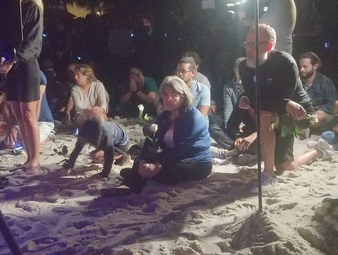 Miami Dade County Mayor Daniella Levine Cava takes part in a meditation ceremony on the beach Monday night near the site of the Champlain South Condo tower collapse site.