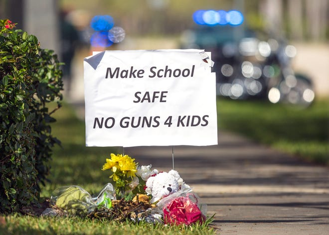 A gun control sign sits down the street from Marjory Stoneman Douglas High School as students and their parents arrived Wednesday morning, February 28, 2018. (Lannis Waters /T he Palm Beach Post)