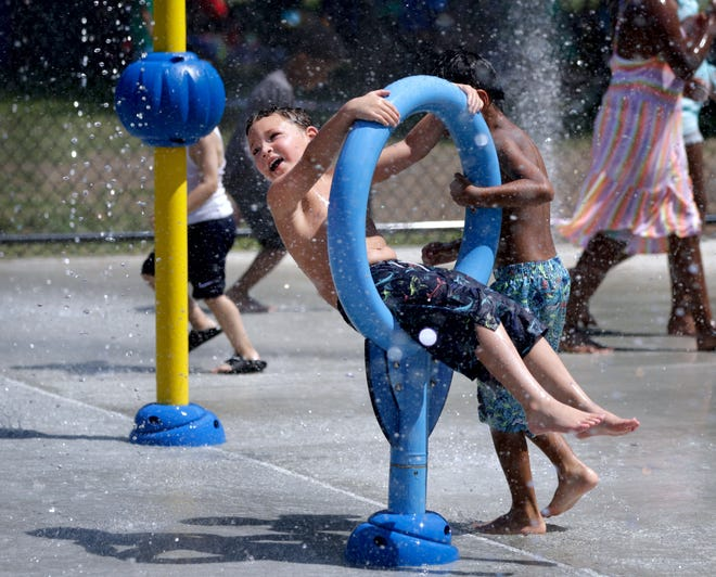 Jayce Horan is spun around in a water-spraying hoop by older brother Adrian Machado at the newly opened waterpark at Pierce Memorial Field in East Providence on Tuesday afternoon.