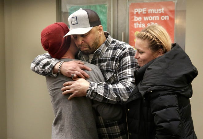 At the Providence Journal offices in December 2018, Mark Gonsalves, center, gets a hug from Jeff Nichols and Ashley Brophy, two of the three people who saved his life by pulling him from the water after he attemped suicide by jumping off the Pell Bridge.