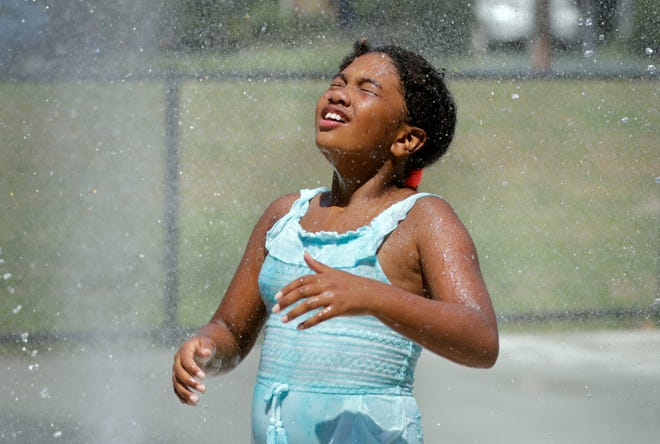 Jordyn Braxton envelops herself in a cooling mist from multiple fountains Tuesday afternoon at the waterpark.