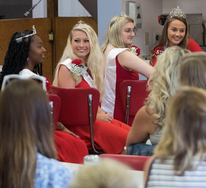 While seated at the counter of Heggy's Confectionary in Alliance, members of the 2019 Carnation Festival court,  from left, Third Attendent Ke'Aijah Hawkins; Second Attendent Bailey Balderson; First Attendent Kylie Dean; and Queen Allison Waggoner, speak to the 2021 candidates Sunday June 27, 2021, at the contest kickoff meeting.