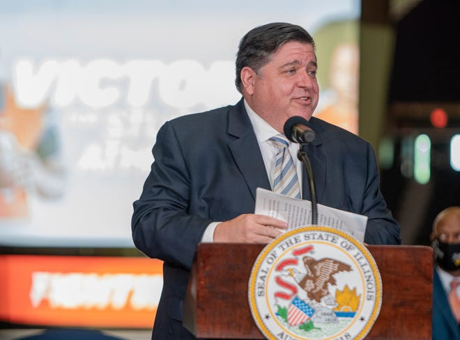 Gov. JB Pritzker speaks at State Farm Center on the University of Illinois campus in Urbana on Tuesday. He spoke before signing a bill that allows college athletes in the state to profit off of their name, image and likeness.