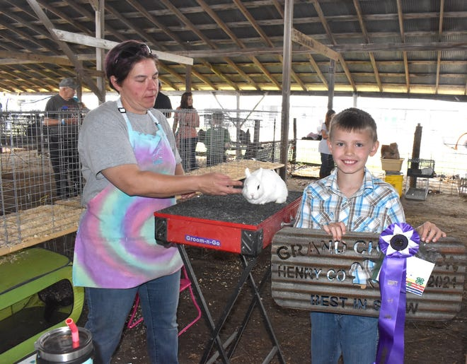 Judge Mandy Johnson, left, gives the Best in Show award to a purebred Dwarf Hotot rabbit shown by Easton Frank of Hooppole during the 4-H rabbit show on Saturday morning, June 26, at the Henry County Fair. He is a member of the Atkinson Boosters
