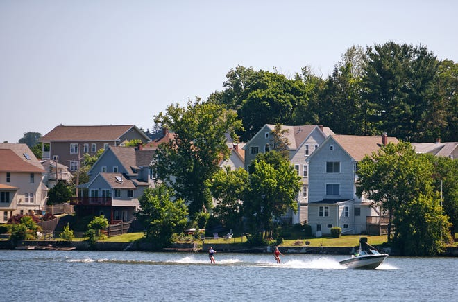 A boat towing skiers passes by homes that line Indian Lake in Worcester on Tuesday.