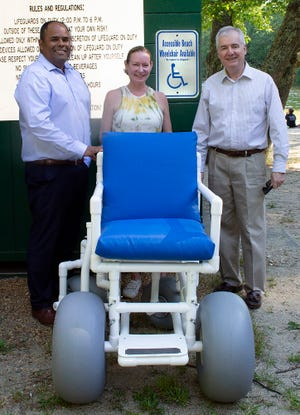 Showing off the accessible beach wheelchair, available at Spectacle Pond, are (from left) Town Administrator Orlando Pacheco, Lancaster Recreation Director Andrea Kiuru-Shepard, and Mike McCue, chairman of the Lancaster Commission on Disability.