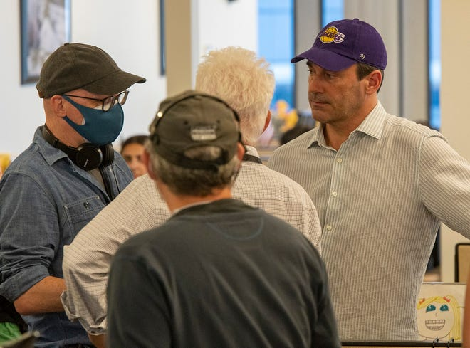 Director Greg Mottola, left, actor John Slattery, center, and actor John Hamm, right, prepare to film a scene in the T&G newsroom Tuesday.