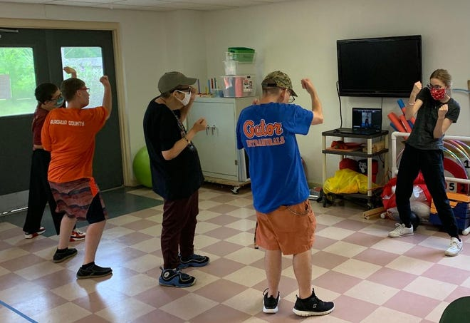 """Arc of Alachua County clients at its 12th Road Home get lessons in the """"sweet science"""" (boxing) from Direct Support Professional Ally Lehman."""