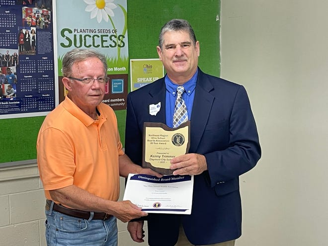 Claymont City Schools board member Kenny Trimmer was presented with a 20-year longevity service award June 28.  Pictured, from left: Reno Contipelli abd Kenny Trimmer.