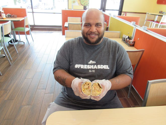 Jordan Schimpf, general manager of Del Taco in Whitehall, displays a chicken burrito at the restaurant, 4720 E. Main St. Del Taco is part of a California-based chain.