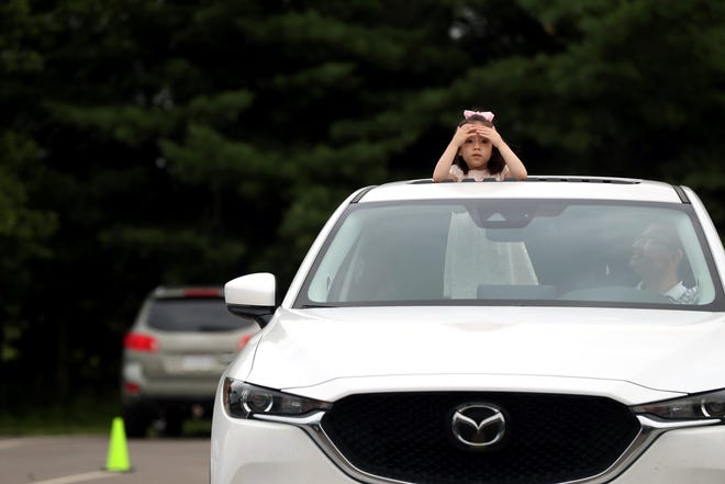 """Mika Page, 4, of Columbus surveys the parking lot at Headley Park in Gahanna with her father, Jonathan Page, before a viewing of """"Monsters, Inc."""" as part of Gahanna Parks & Recreation's summer drive-in movie and concert series June 25."""