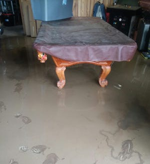 Standing water invades Roy and Trina LaFleur's garage on Williams Avenue in the Village of Wellsville in June.