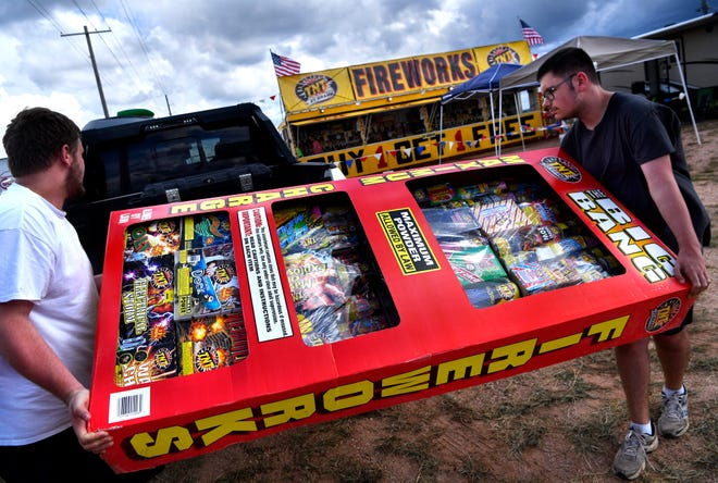 Brothers Jarett (left) and Logan Daniel load a customer's pickup at the TNT Fireworks stand at FM 707 and the Winters Freeway on Monday. The Findley family has operated a stand since 2008.