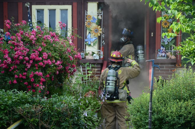 Battle Creek firefighters enter through the smoke at a house fire Monday on Surby Avenue