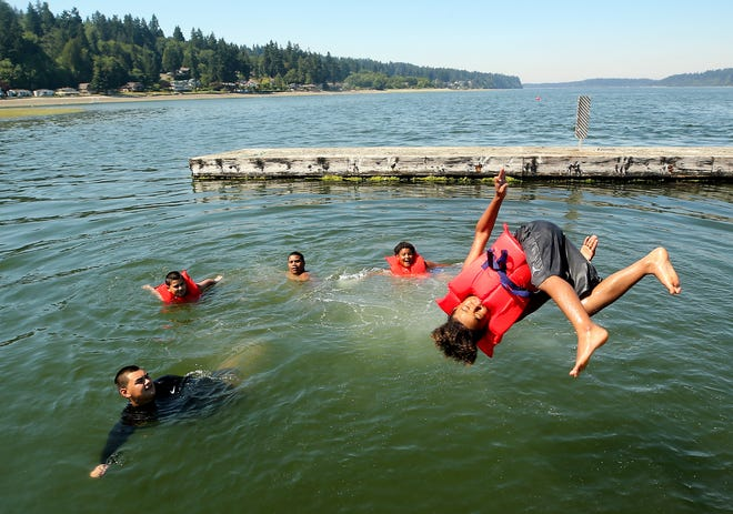 Midas Johnson, 8, performs a flip off of the dock while cooling off in the water with family members at Illahee State Park in Bremerton on a sweltering Monday.